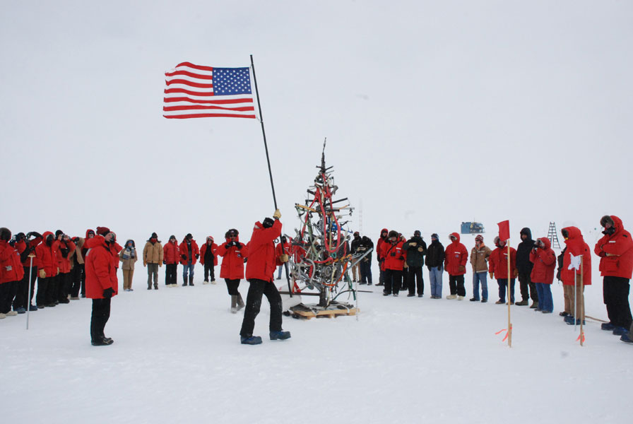 Personnel at Amundsen-Scott South Pole Station move the US flag located at the geographic Pole to its new location.