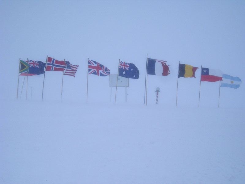 The ceremonial pole is surrounded by flags of the 12 signatory nations of the Antarctic Treaty.